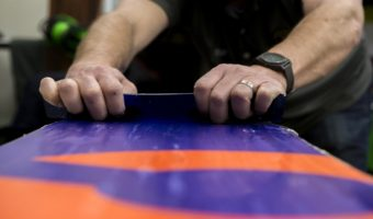 closeup on wax being scrapped off a snowboard