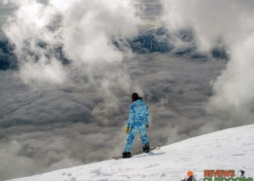 snowboarder on snowboard with best snowboard boots on cloudy snowy mountain