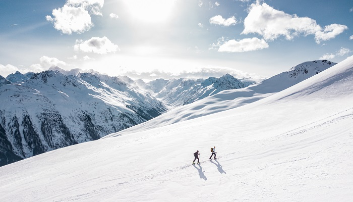 two cross country skiiers on an alpine slope
