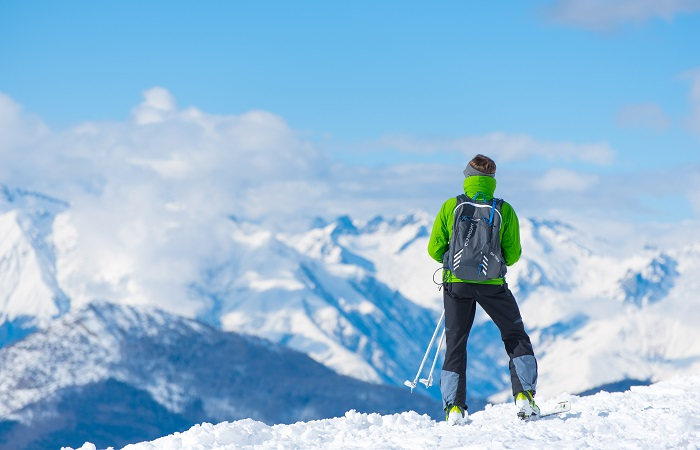 skier on top of a mountain peak admiring the view