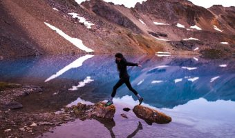 women with best waterproof hiking shoes skipping on rocks