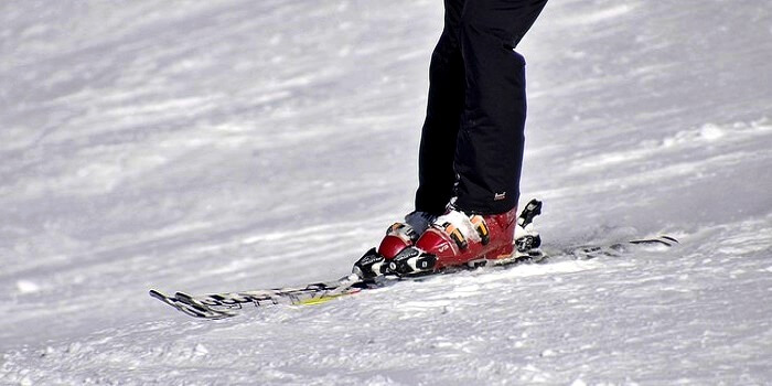 closeup on legs of skier on skis sliding down slopes