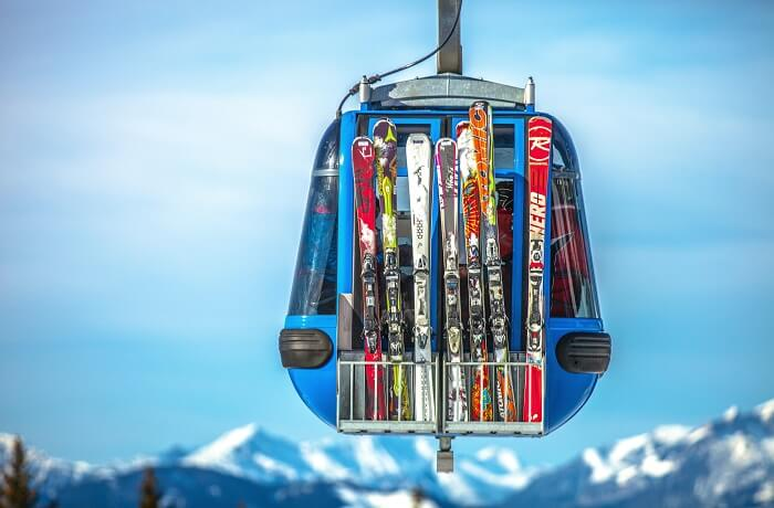 skis on the back of a cable car in mid air