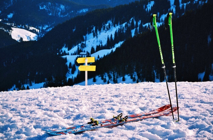 ski and ski poles stuck in snow on slope
