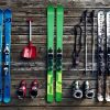three pairs of skis colored differently on wood planks