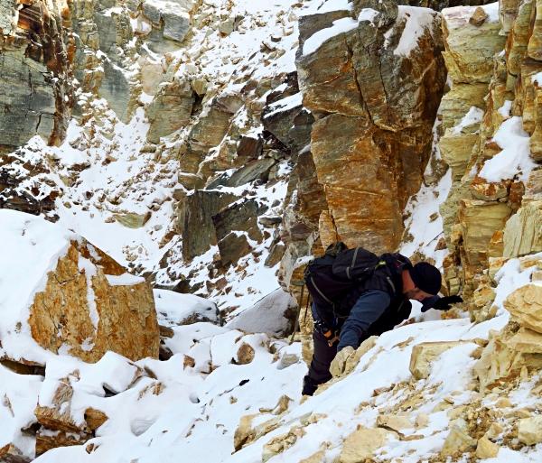 man scrambling on rocks