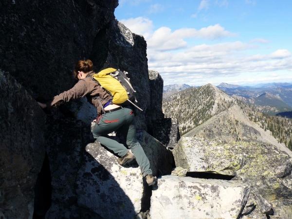 woman scrambling on rocks