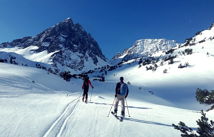 backcountry skiiers on trail in the mountains