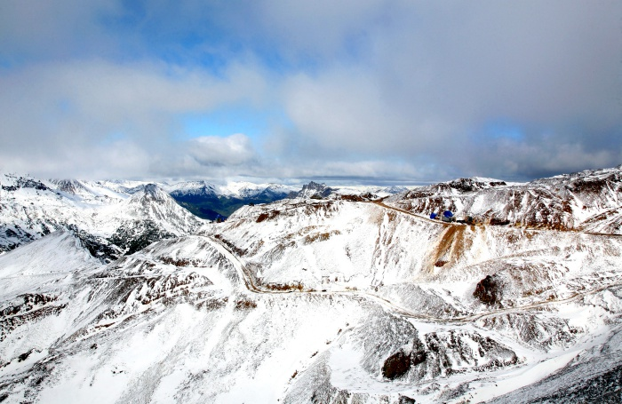 mountain peaks with snowy patches, trails, and bare land patches