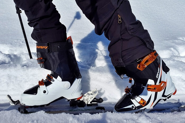 closeup on a pair of ski boots walking in the snow