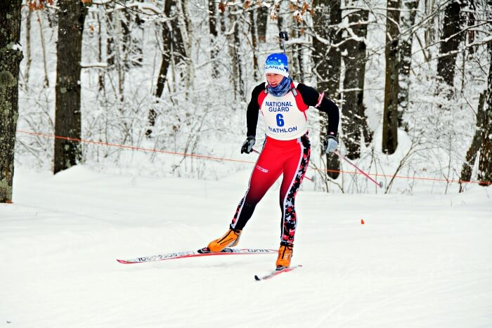 athletic skier skiing in snowy forest