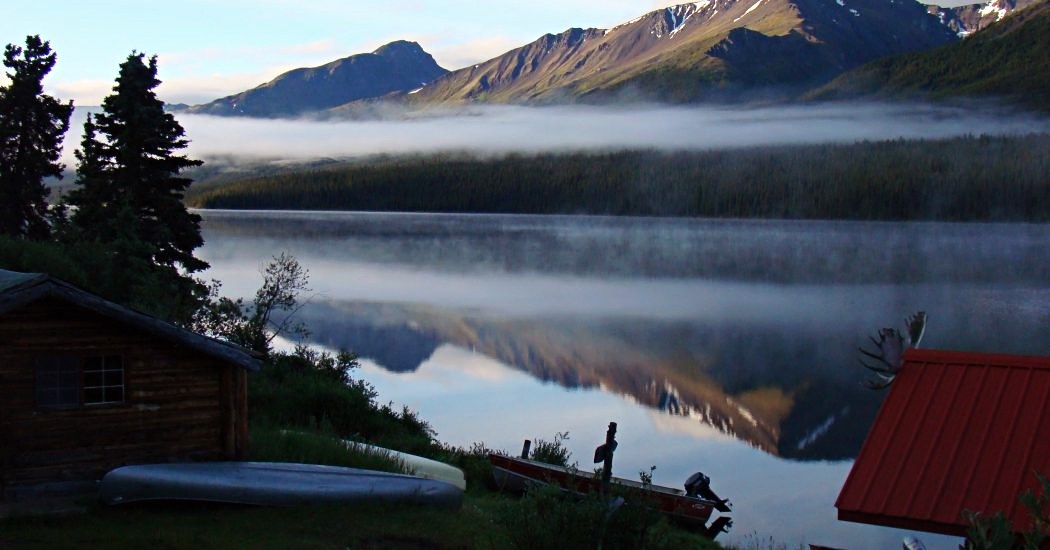 foggy lake and mountains with cabin landscape