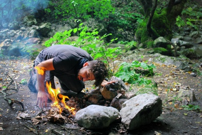 man lighting fire in the firepit in forest