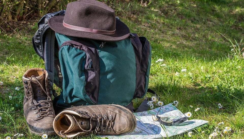 backpacking backpack with hiking shoes and map and hat on grass