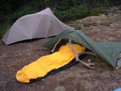 sleeping bag under tarp near tent on ground