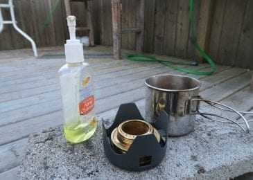 alcohol stove and alcohol bottle near can