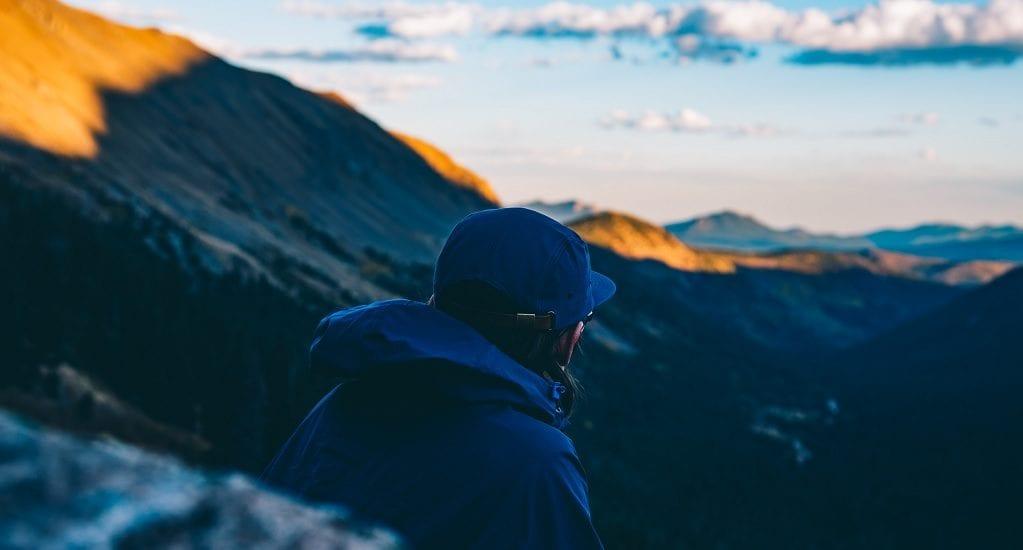 Man wearing rain jacket is gazing at mountains
