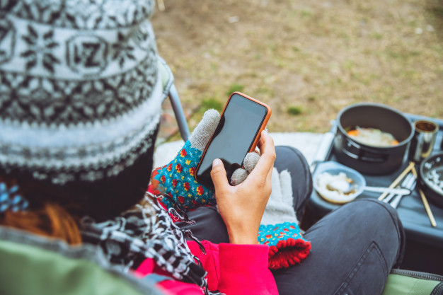 Camper relaxing with smartphone while winter camping