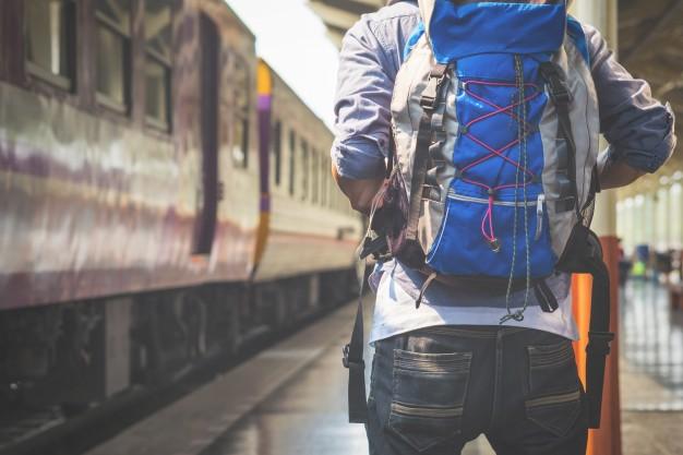 Man carrying ultralight backpack awaiting on railway platform
